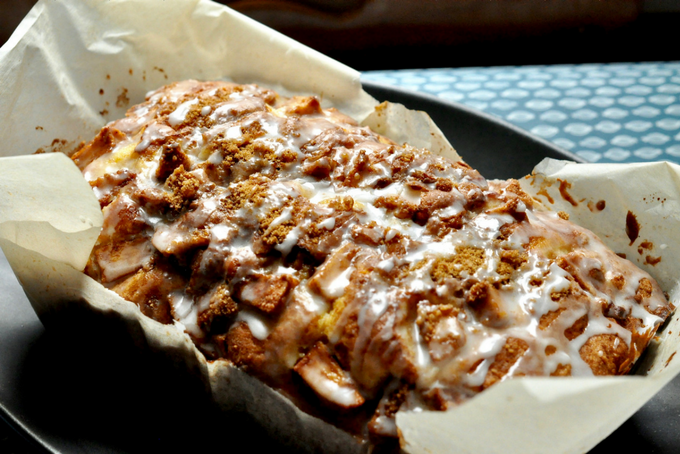 a delicious lactose-free apple fritter loaf with sweet glaze cooling by the window